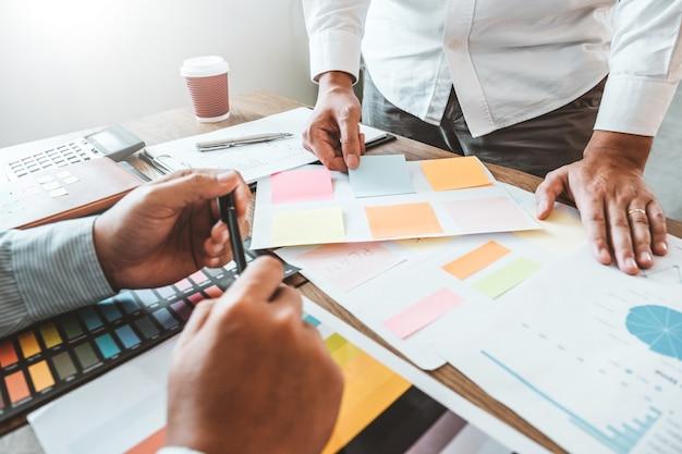 Wielorasowy kreatywny zespół pracujący razem w nowoczesnym biurze śmiejąc się i burzy mózgów