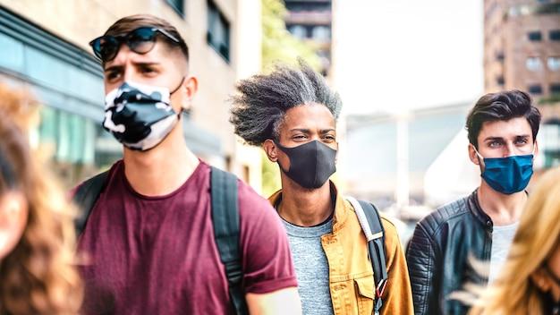 Wielorasowy tłum chodzący ulicą miasta z maskami na twarz
