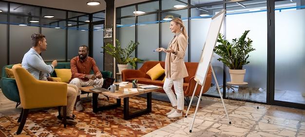 Wielorasowy zespół biznesowy spotykający się w strefie lounge w biurze coworkingowym, o którym rozmawiają