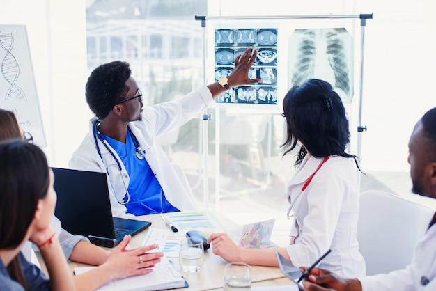 Wielorasowy zespół młodych lekarzy omawiających tomografię komputerową kończy się w klinice