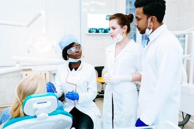 Wielorasowy zespół stomatologiczny z pacjentem w klinice dentystycznej. koncepcja zdrowia jamy ustnej.