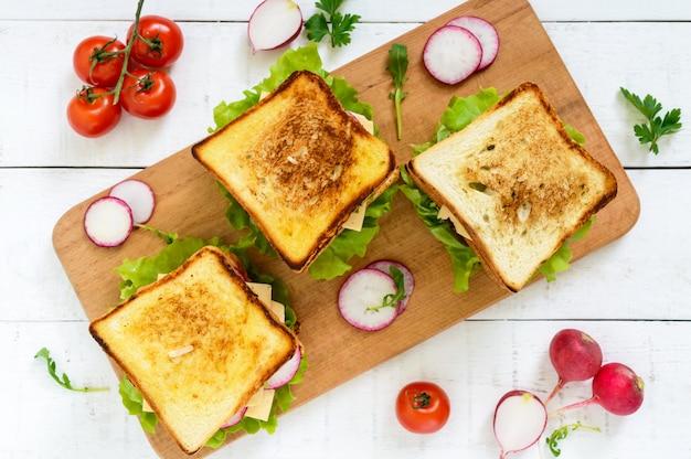 Wielowarstwowe kanapki z soczystym kotletem, serem, rzodkiewką, ogórkiem, sałatą, rukolą na desce do krojenia widok z góry.