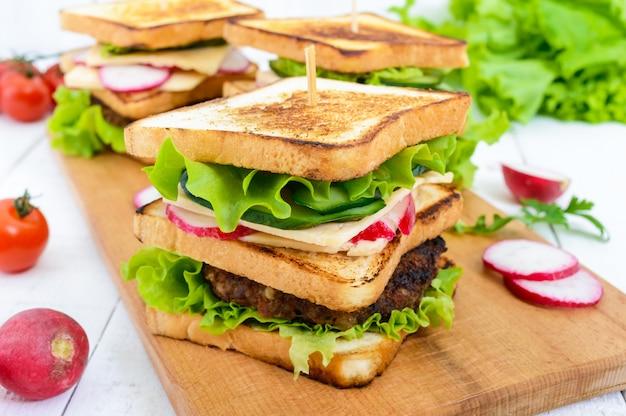Wielowarstwowe kanapki z soczystym kotletem, serem, rzodkiewką, ogórkiem, sałatą, rukolą na desce do krojenia