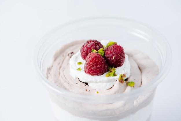 Wielowarstwowy deser kremowy zwieńczony malinami i pistacjami