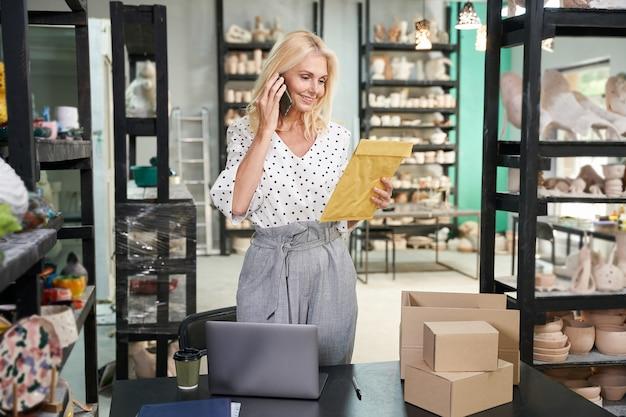 Wielozadaniowość wesoła dojrzała kobieta biznesu, właściciel sklepu rozmawia przez telefon, trzymając kopertę, podczas gdy