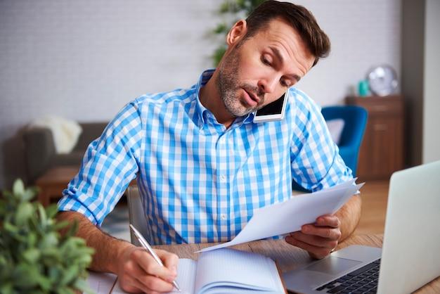 Wielozadaniowy mężczyzna pracujący w domowym biurze