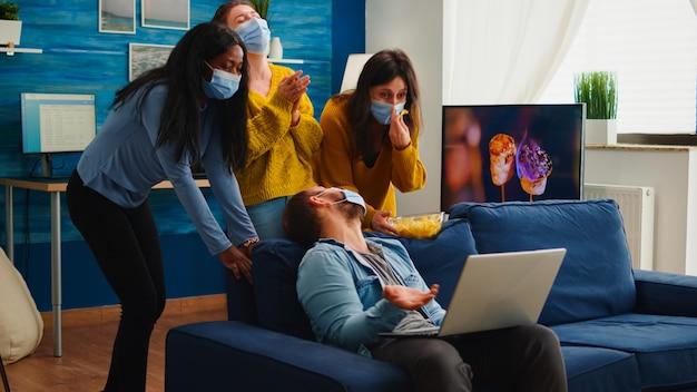 Wielu etnicznych przyjaciół noszących maskę na twarz, jedzących przekąski za pomocą laptopa, utrzymujący dystans społeczny, aby zapobiec rozprzestrzenianiu się koronawirusa podczas globalnej pandemii, bawiąc się w domowym salonie. obraz koncepcyjny.