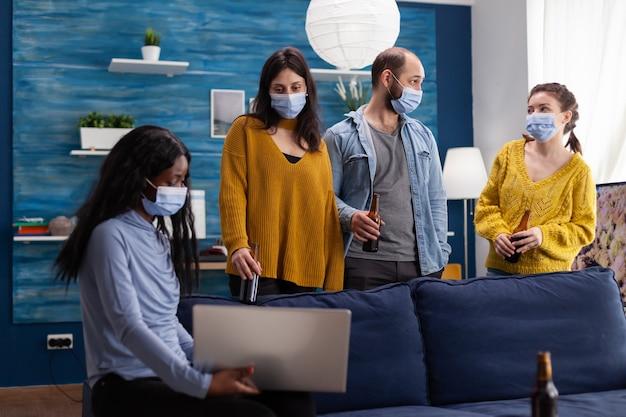 Wielu etnicznych przyjaciół noszących maskę na twarz, pijących piwo za pomocą laptopa, utrzymujący dystans społeczny, aby zapobiec rozprzestrzenianiu się koronawirusa podczas globalnej pandemii, bawiąc się w domowym salonie. obraz koncepcyjny.