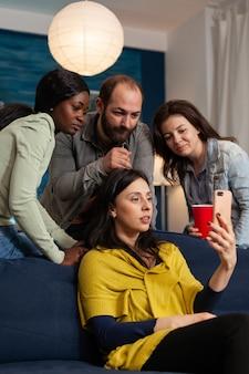 Wielu etnicznych przyjaciół odbywa wirtualną rozmowę wideo na smartfonie i nawiązuje więzi. grupa wielorasowych ludzi spędzających czas razem siedząc na kanapie późno w nocy w salonie.