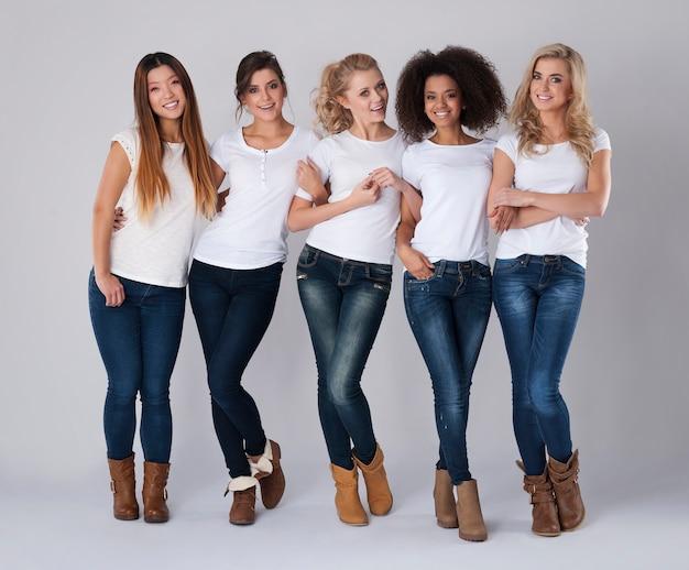 Wielu etnicznych przyjaciół w dżinsach i białych koszulkach