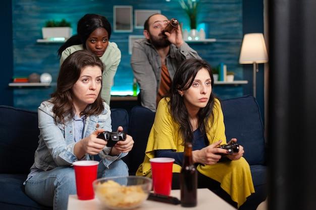 Wielu etnicznych przyjaciół wesoła grupa ludzi relaksuje się na grach konsolowych z kontrolerem
