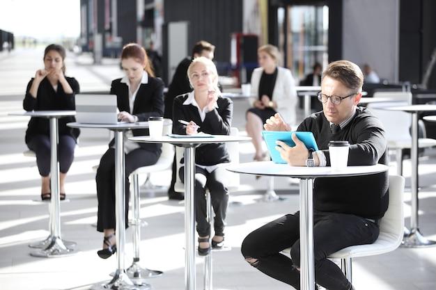 Wielu ludzi biznesu siedzi w kawiarni nowoczesnego biurowca