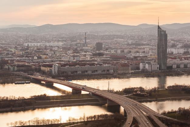 Wien o zachodzie słońca, z dunajem, autostradą i budynkami