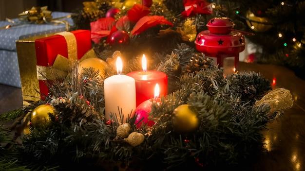 Wieniec adwentowy na stole z płonącymi świecami obok udekorowanej choinki