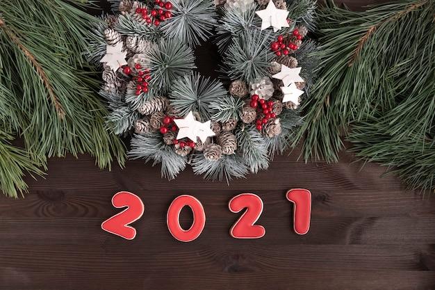 Wieniec bożonarodzeniowy i napis z piernika w 2021 roku na tle drewnianych. koncepcja nowego roku.