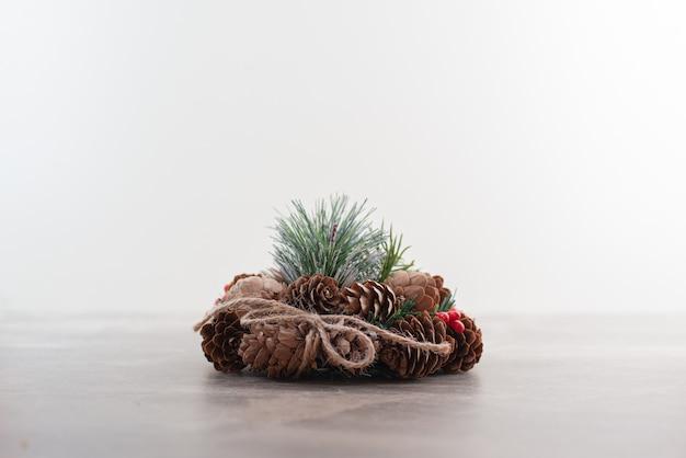 Wieniec bożonarodzeniowy z czerwonymi koralikami i szyszkami na marmurze.