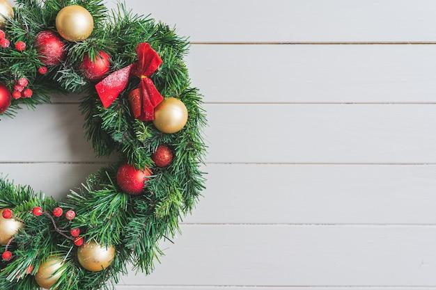 Wieniec bożonarodzeniowy z dekoracjami na białym drewnianym