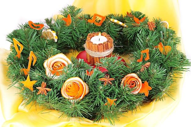 Wieniec bożonarodzeniowy z płonącą świeczką