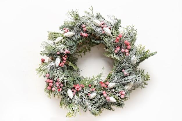 Wieniec bożonarodzeniowy z świeżej naturalnej gałęzi świerkowej z czerwoną dekoracją na białym tle nowy rok