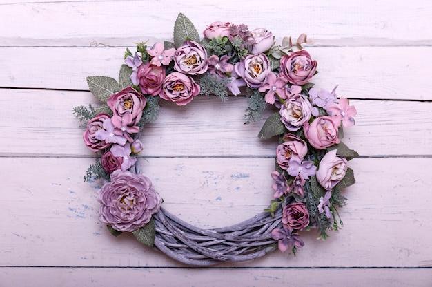 Wieniec drzwiowy wykonany ze sztucznych kwiatów i roślin jesienią na shabi białym drewnianym tle.