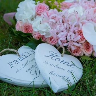 Wieniec kwiatów z symbolami i cytatami na trawie