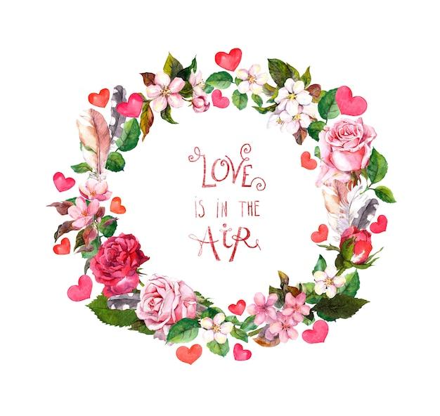 """Wieniec kwiatowy z kwiatami róż i kwiatem wiśni, piórami, różowymi sercami. akwarela okrągła granica na walentynki, wesele z cytatem """"miłość jest w powietrzu"""""""