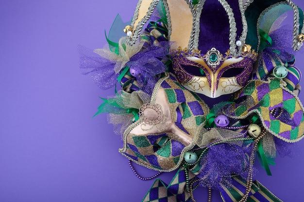 Wieniec mardi gras na fioletowym tle z maską mardi gras. widok z góry
