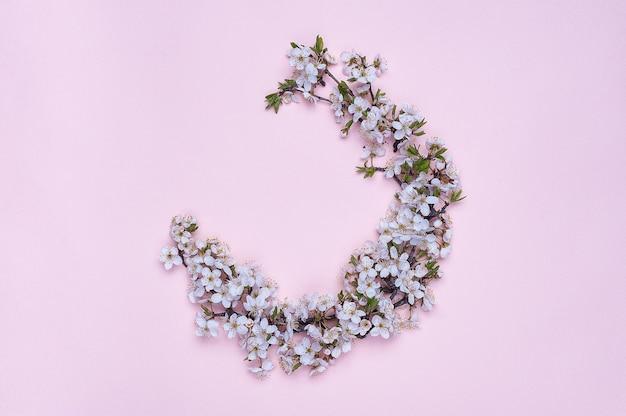 Wieniec okrągły wykonany z wiosennych kwiatów na różowym tle.
