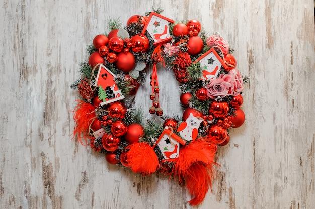 Wieniec świąteczny ozdobiony czerwonymi kulkami, kokardkami, różami i domkami z zabawkami