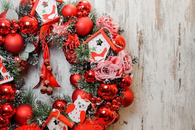 Wieniec świąteczny ozdobiony czerwonymi kulkami, różami i domkami z zabawkami
