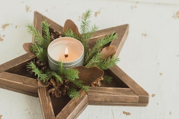 Wieniec świąteczny w drewnianej tacy w kształcie gwiazdy ze świecami. świąteczny wystrój z elementami w stylu rustykalnym