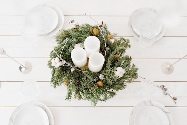 Wieniec świąteczny z białymi świecami na świątecznym stole z talerzami