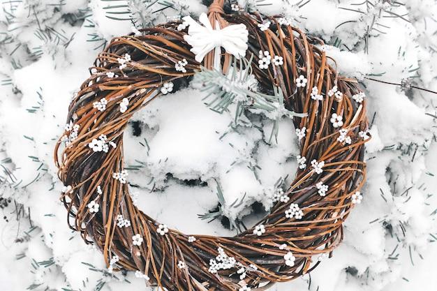 Wieniec świąteczny z gałęzi. ręcznie robiony wieniec na drzwiach w śniegu. zimowy wystrój