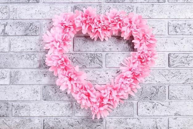 Wieniec w kształcie serca zdobiony sztucznym kwiatem wykonanym z różowych serwetek z bibuły