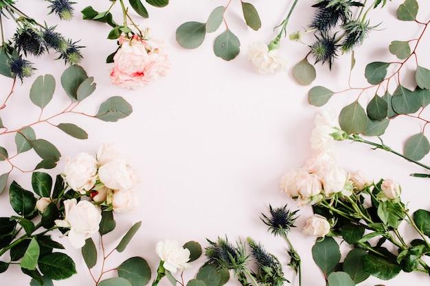 Wieniec w okrągłej ramie z beżowych kwiatów róży, kwiatu eringium, gałęzi eukaliptusa i liści na bladym, pastelowym różu