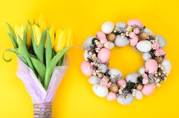 Wieniec wielkanocny z kolorowymi ozdobnymi jajkami i kwiatami
