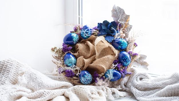 Wieniec wielkanocny z niebieskimi jajkami z cekinami w oknie.
