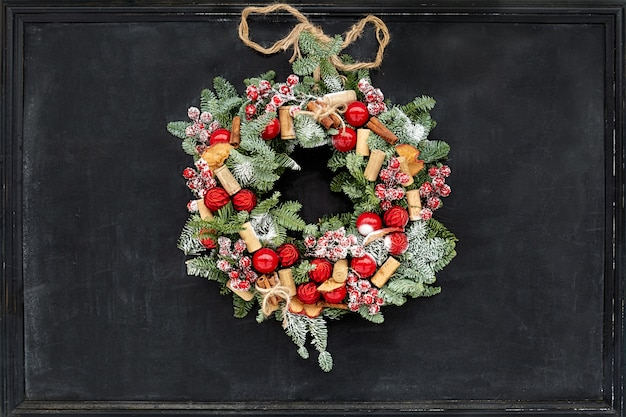 Wieniec wykonany z gałęzi jodłowych, suszonych jabłek, cynamonu, czerwonych jagód, kapsli, czerwonych kulek zawieszonych na czarnej tablicy kredowej.