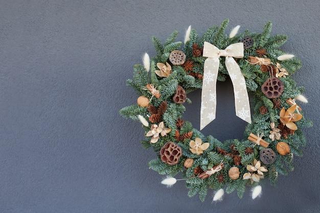 Wieniec wykonany z naturalnych gałęzi jodły wiszących na szarej ścianie. wieniec z naturalnymi ozdobami: guzki, orzechy włoskie, cynamon, szyszki. nowy rok i ferie zimowe. świąteczny wystrój. skopiuj miejsce