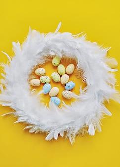 Wieniec z białych piór na żółtym tle z mini sztucznymi jajkami, widok z góry. koncepcja dekoracji wielkanocnych