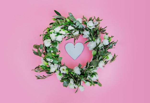 Wieniec z białych róż i serca na różowym tle. ozdobiony. powyżej widok