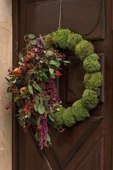 Wieniec z czerwonymi jagodami i suchymi liśćmi i owocami wiszący na drzwiach.