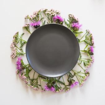 Wieniec z dzikich fioletowych i różowych kwiatów na szaro. leżał płasko.