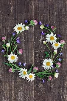 Wieniec z rumianków i prostych kwiatów na tle starego drzewa