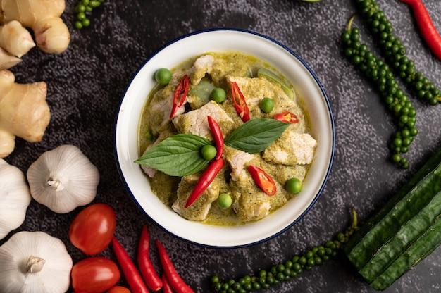 Wieprzowe zielone curry w białej misce z przyprawami na czarnym tle cementu