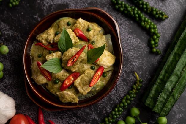 Wieprzowe zielone curry w brązowej misce z przyprawami na czarnym tle cementu