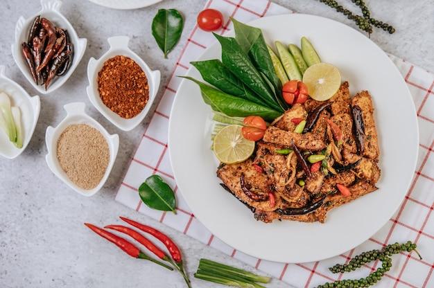 Wieprzowina nam tok ze smażonym chili, pomidorem, limonką, ogórkiem i świeżą papryką. tajskie jedzenie.