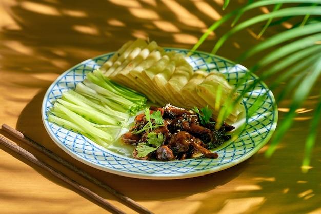 Wieprzowina po pekińsku lub kaczka z mizerią i chińskim chlebem na talerzu. chiński kuzyn