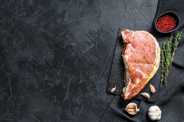 Wieprzowina z kością. kotlet do smażenia na grillu. z przyprawami i składnikami czosnek. surowe mięso ekologiczne. czarne tło. widok z góry. skopiuj miejsce
