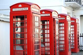 Wiersz czerwonych budek telefonicznych w londyńskiej ulicy